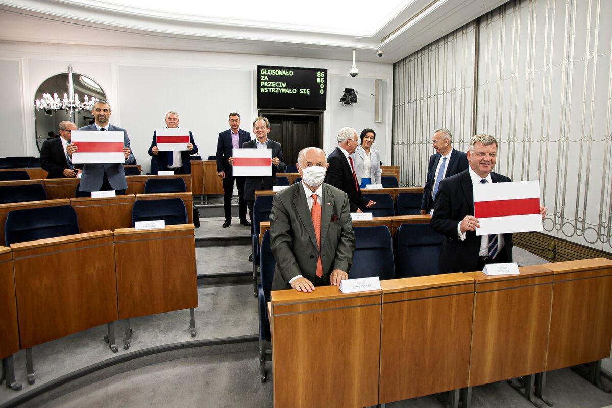 Senatorowie trzymający biało-czerwono-białe barwy Białorusi