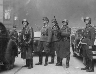 Pozujący niemieccy żołnierze, a w tle płonące warszawskie getto....